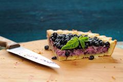 Last piece of blueberry pie decorated with basil leaves and knif Royalty Free Stock Image