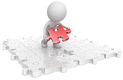 Last piece. The dude putting last puzzle piece in assembly. Red Royalty Free Stock Images