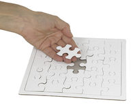 The last piece of the Jigsaw. Female hand holding a piece of jigsaw in one hand against a white jigsaw puzzle, showing a space for the last piece, isolated on a Royalty Free Stock Photography