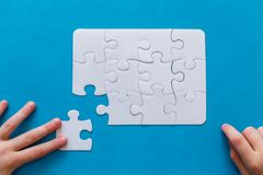 Last piece jigsaw in hand,Concept success of business. Last piece jigsaw in hand. Concept success of business. Blue background Stock Images