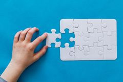 Last piece jigsaw in hand,Concept success of business. Last piece jigsaw in hand. Concept success of business. Blue background Stock Image