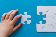 Last piece jigsaw in hand,Concept success of business. Last piece jigsaw in hand. Concept success of business. Blue background Stock Photography