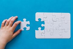 Last piece jigsaw in hand,Concept success of business. Last piece jigsaw in hand. Concept success of business. Blue background Royalty Free Stock Images