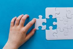 Last piece jigsaw in hand,Concept success of business. Last piece jigsaw in hand. Concept success of business. Blue background Royalty Free Stock Photos