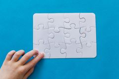 Last piece jigsaw in hand,Concept success of business. Last piece jigsaw in hand. Concept success of business. Blue background Royalty Free Stock Photo