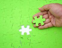 The last piece of jigsaw puzzle. A hand providing the last piece of jigsaw puzzle Stock Image