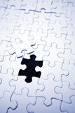 Last piece of jigsaw puzzle. Details of nearly completed blank white jigsaw puzzle, with remaining piece visible Royalty Free Stock Photo