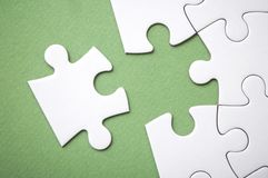 The last piece of jigsaw puzzle missing on green background to complete the mission. Closeup of the last piece of jigsaw puzzle missing on green background to royalty free stock image