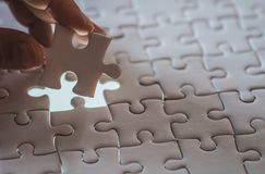 Last piece of white plain jigsaw holding by hand. Step of success concept Royalty Free Stock Images