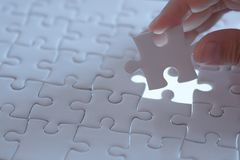 Last piece of white plain jigsaw holding by hand. Step of success concept Stock Photo