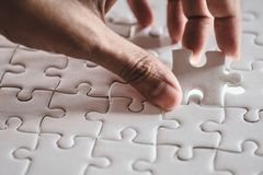 Last piece of white plain jigsaw holding by hand. Step of success concept Royalty Free Stock Image