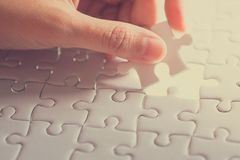 Last piece of white plain jigsaw holding by hand. Step of success concept Royalty Free Stock Photo