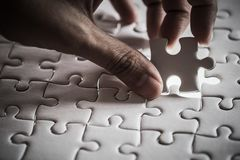 Last piece of white plain jigsaw holding by hand, step of success concept, dramatic. Tone Stock Images