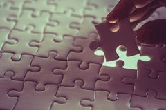 Last piece of white plain jigsaw holding by hand. Step of success concept Stock Image