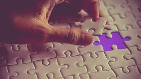 Last piece of white plain jigsaw holding by hand, step of success concept. Ultraviolet tone Stock Photos