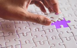 Last piece of white plain jigsaw holding by hand, step of success concept. Ultraviolet tone Stock Photo