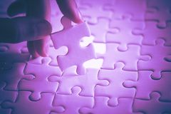 Last piece of white plain jigsaw holding by hand, step of success concept, ultraviolet. Tone Royalty Free Stock Image
