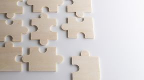 Last piece of wooden jigsaw is almost in place for business solu. Puzzles on a wooden background. Concept business. Idea: working in a team. Close up stock photo