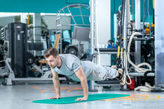 Last pushups. Young and handsome athlete doing pushups in the gy Royalty Free Stock Photos