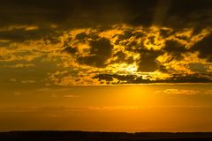 Last rays of setting sun painted sky in yellow and orange colors stock photography
