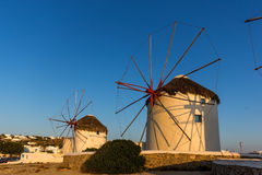 The last rays of the sun over White windmills on the island of Mykonos, Greece Stock Images