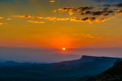Sunset over the rocky ridge. The last rays of the sun shine from behind the rocky ridge and illuminate the sunset rays Royalty Free Stock Photos