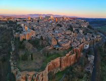 The last rays of sunlight hit the tall buildings of an Italian hilltop town. stock photos