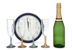 The last seconds till New Year. Champagne, three glasses and clock on white background. The pointers on a clock shows one minute to midnight (or twelve o'clock Stock Photos
