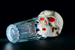 Last sip. Lit skull with orange eyes next to empty glass, laying in front of it,  on dark background Royalty Free Stock Photography