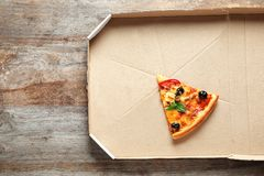 Last slice of tasty pizza in cardboard box. On wooden table, top view stock photos