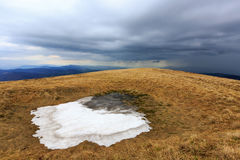 Last snow on meadow in mountains Stock Photo