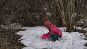 The last snow of the season. Girl child playing snowballs with the last snow. Spring, the snow is almost everywhere melted. Only i stock video footage