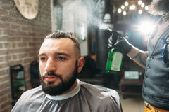 Last step of haircut - barber spray client. Free space. Portrait of young men sitting at barbershop and making stylish hairdo. Beauty, modern life, business Royalty Free Stock Photography