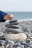 Last stone. Tower made of pebbles on the beach with childs hand Royalty Free Stock Images