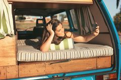At Last! Summer Holidays!. Summer holidays, road trip, travel and people concept, young woman resting in minivan car stock photography