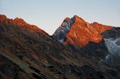 Last sunrays on the peak of mountain Stock Photo