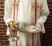 Last supper. Cup and bread in the hands of a pastor. Ready for communion Royalty Free Stock Images