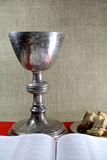 The last supper. Old chalice and open Bible on red background stock images