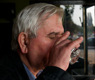 The Last Swig. Older man drinking last gulp of grapebrandy in workers' cafe, Zagreb, Croatia Stock Photo