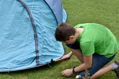 Last tent peg. Teenage boy banging in tent pegs. Fixing the tent on the ground Royalty Free Stock Photos