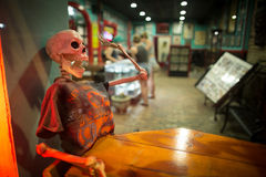 Last to Leave New Orleans. A skeleton in a t-shirt sits at a wooden table in the window of a tattoo parlor on Frenchman Street in New Orleans, Louisiana Stock Photography