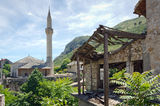 The Last Traces of War. Building destroyed by War in Mostar, Bosnia and Herzegovina. In the background is a mosque Stock Photography
