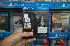 The Last of Us remastered. Bratislava, Slovakia, circa april 2017: Man holding The Last of Us remastered videogame on Sony Playstation 4 console in store Royalty Free Stock Images