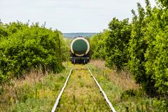 Last wagon tank of freight train on a single track railroad. In a green bushes Stock Images