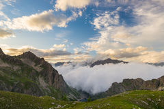 Last warm sunlight on alpine valley with glowing mountain peaks and scenic clouds. Italian French Alps, summer travel destination. Royalty Free Stock Photography