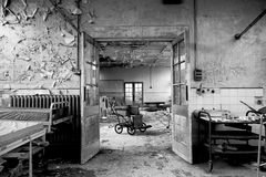 Last wheelchair on the Ward. Wheelchair is framed perfectly by the doors and represents the age and emptiness of the hospital royalty free stock photo