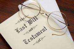 Last Will. And testament, wire rim glasses shot on warm wood surface stock photography