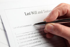 Last Will. An elderly woman's hand filling out a last will and testament document stock images