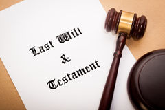 Last Will and Testament. A gavel and soundboard on top of a 'Last Will and Testament' contract, with a antique-like background stock photos
