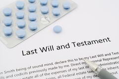Last will and testament with blue pills and grey pen Stock Photo